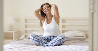 Young adult woman in plaid pajamas sitting on bed