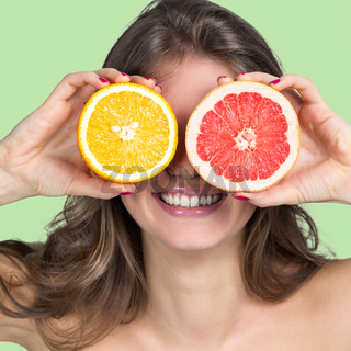 Smiling woman holding citrus slices