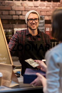 happy barman and woman paying money at cafe