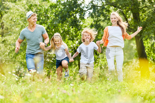 Familie und Kinder laufen über eine Wiese