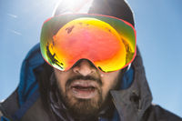A portrait of a bearded man wearing ski goggles on his way to the top of the mountain. The concept of endurance in the way