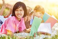 Asiatisches Mädchen macht Hausaufgaben im Garten