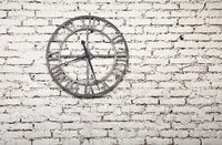 Old metal clock on white painted grunge brick wall