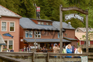 People Looking for Salmon and Photographing while Enjoying Visit of Creek Street in Ketchikan Alaska