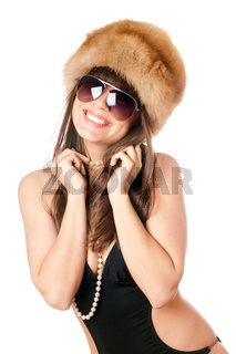 Smiling woman in black swimsuit and fur-cap. Isolated