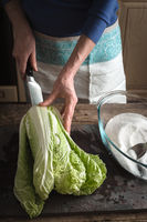 Woman cut Chinese cabbage to cook kimchi on slate