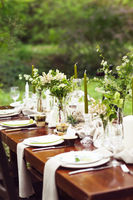 Decoration of wedding table with crystal vases, flowers and branches in botanical style