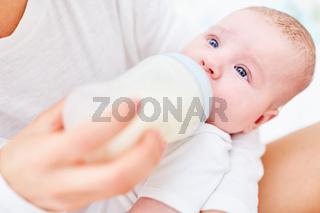 Säugling trinkt Muttermilch aus der Flasche
