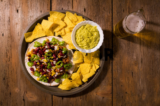 Mexican tortillas with meat, red beans, Jalapeno pepper, nachos chips, beer and salsa guacamole