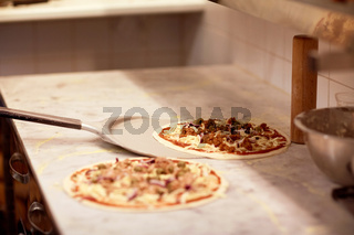 peel taking pizza off table at pizzeria