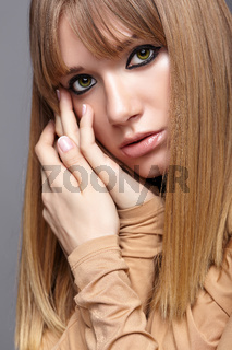 Portrait of blonde young woman. Female with green eyes and long hair. Girl dressed in beige dress on gray background.