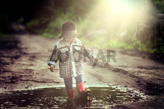 Small boy playing outdoor in summer forest. 3 years old boy in hat playing in nature.