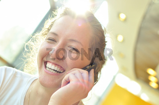 beautiful cheerful woman is talking phone in sunny cafe