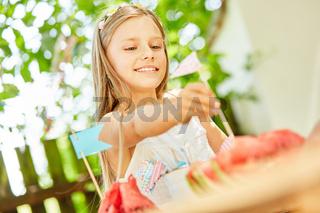 Mädchen dekoriert Wassermelonen mit Fähnchen