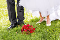 Bridal bouquet is in front of bride and groom in the meadow