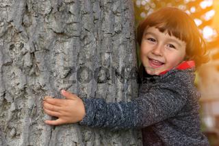 Kind umarmt Baum Umweltschutz Liebe Naturschutz draußen Natur umarmen
