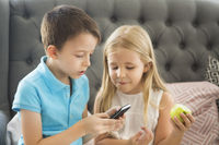 Little brother and sister on the sofa playing mobile phone togethe