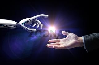 robot and human hand flash light over black