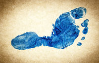 Real imprint of child foot in blue color on real paper in vintage style