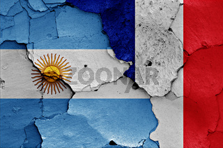 flags of Argentina and France painted on cracked wall