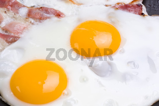detail of ham and eggs in a pan