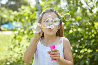 Mädchen pustet Seifenblasen im Sommer