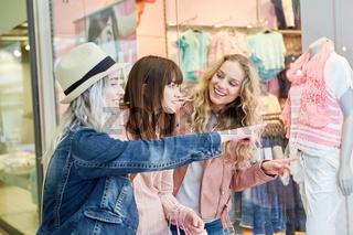 Freunde beim Shopping vor einer Boutique