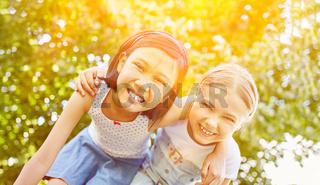 Zwei lachende Mädchen als Freundinnen im Sommer