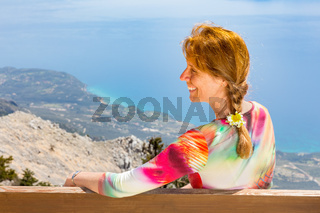 Middle aged woman looking at sea and coast