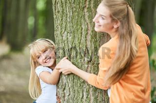 Mädchen spielt mit der Mutter verstecken