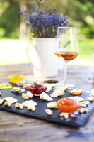 Grape, set of different kind of cheeses with a glass of pink wine on the table