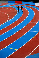 Runners on a red and blue striped athletic track