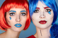 Portrait of young women in comic pop art make-up style. Females in red and blue wigs on blue background