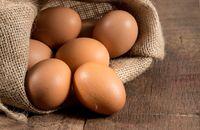 Freshly laid organic eggs in burlap sack on wood
