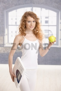 Attractive girl holding apple and scale in hands