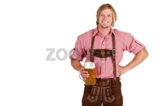 Bayerischer Mann mit Lederhose hält Oktoberfest Maß Bier in der