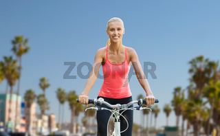 happy young woman riding bicycle outdoors