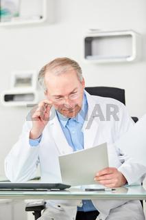 Oberarzt liest ein Dokument am Schreibtisch