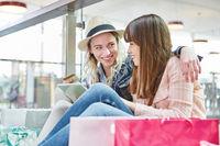 Zwei junge Frauen kaufen im Internet ein