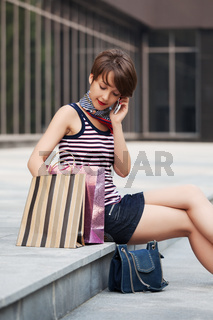 Happy young fashion woman with shopping bag calling on phone next to mall windows