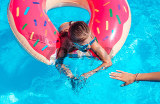 Girl on inflatable ring in swimming pool