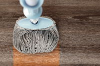 washing dirty wood floor with big mop