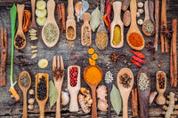 Various of spices and herbs in wooden spoons. Flat lay of spices ingredients chilli ,pepper corn, garlic, thyme, oregano, cinnamon, star anise, nutmeg, mace, ginger and bay leaves on shabby wooden.