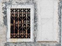 Fenster mit verschnörkeltem Eisengitter in einem weißen Haus in Kroatien
