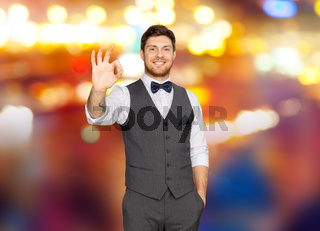 man in suit showing ok sign over night city lights