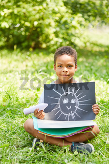 Afrikanischer Junge zeigt Kreide Bild einer Sonne