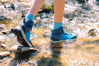 Hiking shoes - sole of trekking boots and legs in a mountain stream