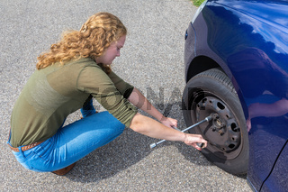 Young dutch woman changing car tire on road