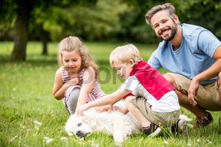 Glückliche Familie mit Hund im Park