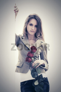 Sad young fashion woman with red roses standing at the wall